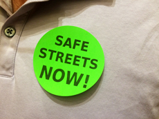 """Residents at the rally were given """"Safe streets now!"""" stickers."""